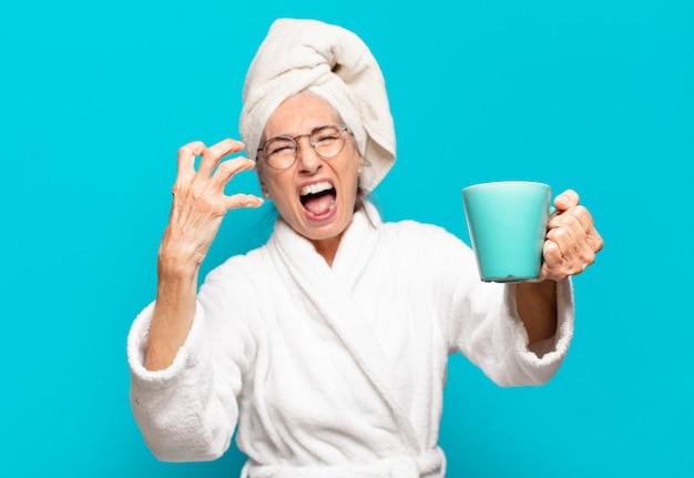Starszy pretty woman ma na sobie szlafrok i kawę