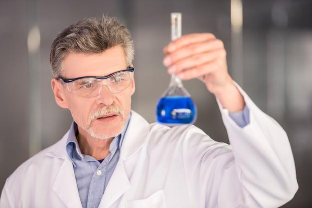 Starszy profesor chemii gospodarstwa kolby z niebieskim płynem.