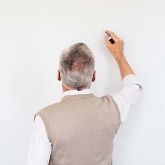 Starszy profesor pisze na pustej tablicy znaczników