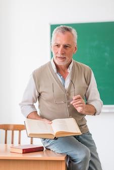 Starszy profesor siedzi na biurku z książką w klasie
