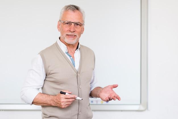 Starszy profesor wyjaśniający stojąc w pobliżu tablicy rejestracyjnej