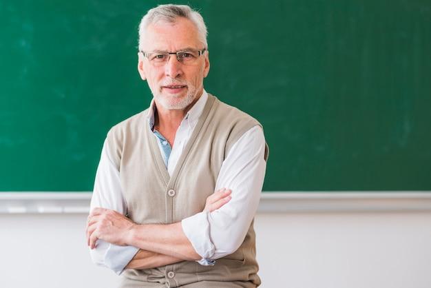Starszy profesor z rękami krzyżował patrzeć kamerę przeciw pustej chalkboard