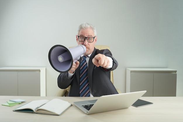 Starszy przedsiębiorca korzystający z megafonu