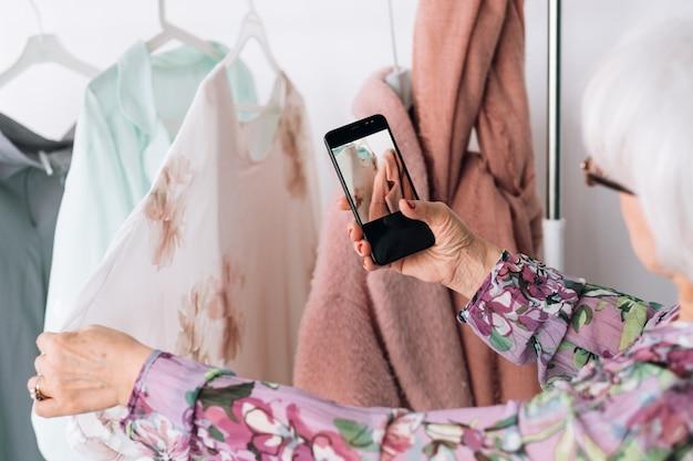 Starszy przegląd stylu mody. zakupy garderoby. starsza pani biorąca mobilne zdjęcie przy wyborze stroju.