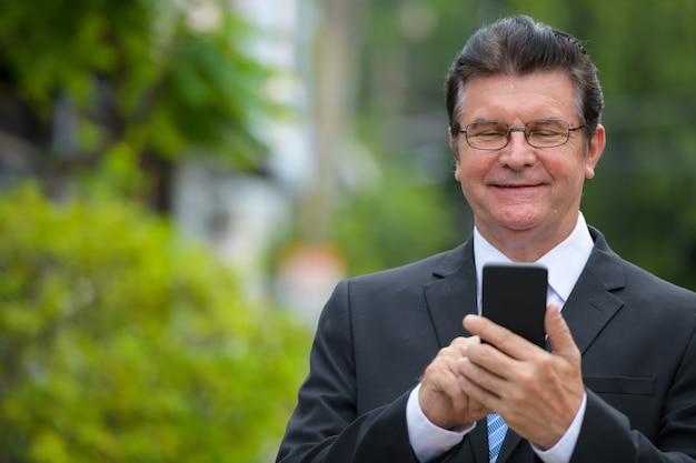 Starszy przystojny biznesmen uśmiecha się podczas korzystania z telefonu