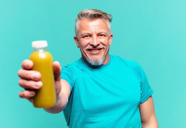 Starszy przystojny mężczyzna pijący wegański koktajl