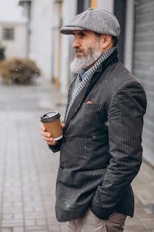 Starszy przystojny mężczyzna pije kawę poza ulicą