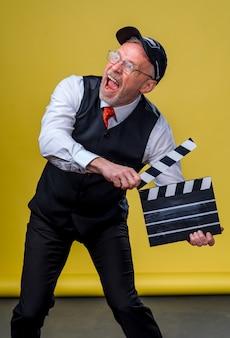 Starszy przystojny mężczyzna trzyma kino klakier. mężczyzna ubrany w garnitur bez kurtki. osoba na białym tle na żółtym tle.