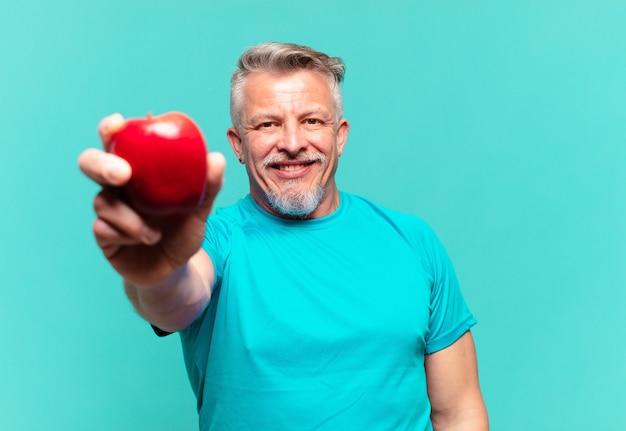 Starszy przystojny mężczyzna z jabłkiem