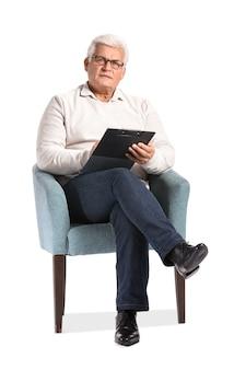 Starszy psycholog mężczyzna siedzi w fotelu na białym tle