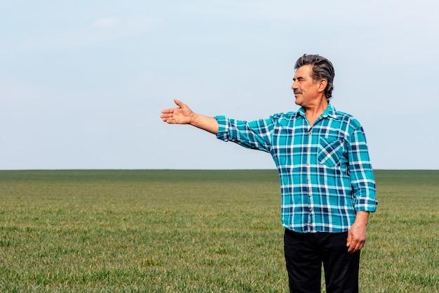 Starszy rolnik klęka na zielonym polu pszenicy z wyciągniętą ręką, przygląda się wiosennym uprawom.
