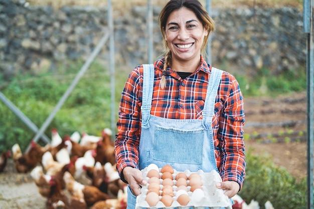 Starszy rolnik kobieta zbierając organiczne jaja w kurniku - styl życia w gospodarstwie i koncepcja zdrowej żywności - skoncentruj się na twarzy