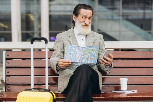 Starszy siwobrody mężczyzna siedzi na ławce z walizką, patrzy na mapę miasta i telefon w budynku lotniska