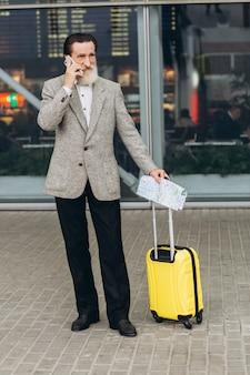 Starszy siwobrody mężczyzna z walizką i mapą miasta bierze telefon i idzie wzdłuż budynku lotniska. patrzy na bok zamyślony. skopiuj miejsce po prawej stronie
