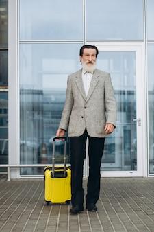 Starszy siwobrody mężczyzna z walizką i mapą miasta idzie wzdłuż budynku lotniska. patrzy na bok zamyślony. skopiuj miejsce po prawej stronie