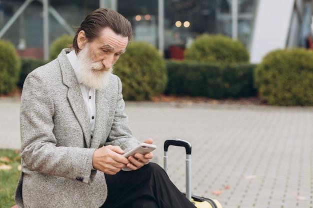 Starszy siwobrody mężczyzna z walizką i mapą miasta siedzi i rozmawia przez telefon w budynku lotniska. patrzy na bok zamyślony. skopiuj miejsce po prawej stronie