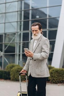 Starszy siwobrody mężczyzna z walizką i smartfonem idzie wzdłuż budynku lotniska. patrzy na bok zamyślony. skopiuj miejsce po prawej stronie