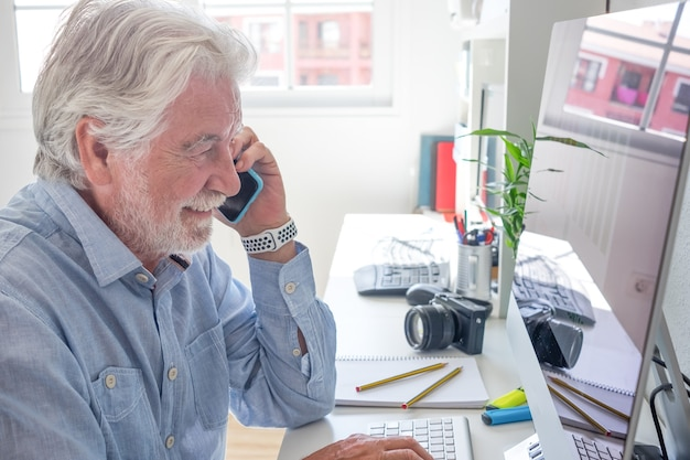 Starszy siwowłosy mężczyzna przy użyciu telefonu komórkowego pracuje na komputerze. biały pulpit