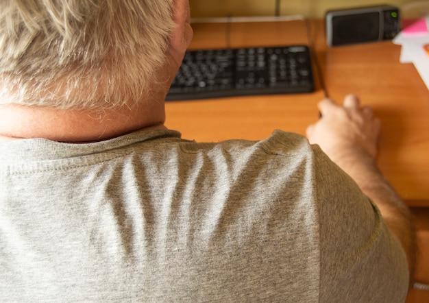 Starszy siwowłosy mężczyzna używa myszy komputerowej