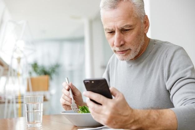 Starszy siwy biznesmen brodaty siedzieć w kawiarni zjeść obiad i zjeść sałatkę za pomocą telefonu komórkowego.