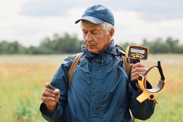 Starszy siwy mężczyzna ubrany w niebieską kurtkę i czapkę pozuje na zewnątrz na polu lub łące i trzyma monetę w rękach, szukając artefaktów za pomocą wykrywacza metalu