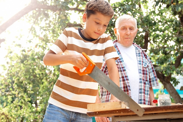 Starszy siwy starszy mężczyzna i teen chłopiec stoją przy stole z narzędziami stolarskimi. dziadek uczy wnuka piłowania deski w ogrodzie w słoneczny dzień.