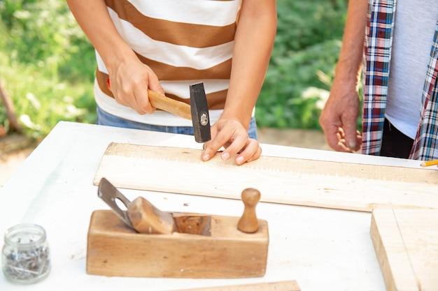 Starszy siwy starszy mężczyzna i teen chłopiec stoją przy stole z narzędziami stolarskimi. dziadek uczy wnuka wbijania gwoździ w ogrodzie w słoneczny dzień. zamknij się, selektywne focus.