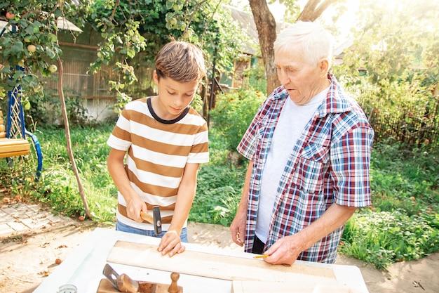 Starszy siwy starszy mężczyzna i teen chłopiec stoją przy stole z narzędziami stolarskimi. dziadek uczy wnuka wbijania gwoździ w ogrodzie w słoneczny dzień.