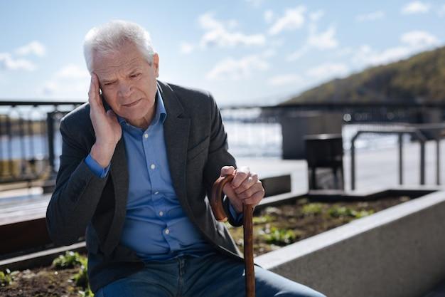 Starszy słaby przystojny mężczyzna odczuwa straszny ból trzymając rękę na skroni i naciskając kij