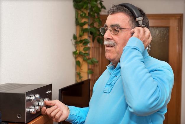 Starszy słuchanie muzyka z nowożytnymi hełmofonami w domu