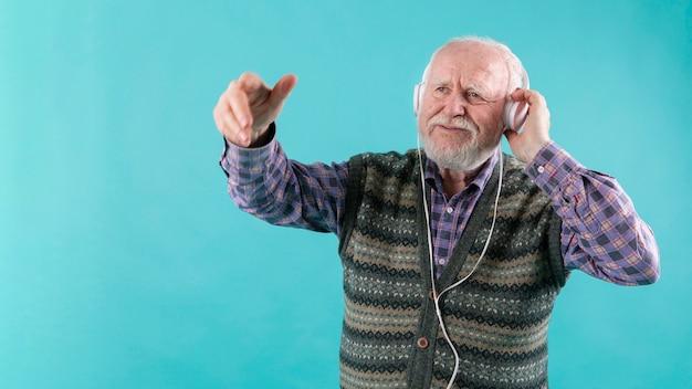 Starszy słuchanie muzyki w przestrzeni kopii