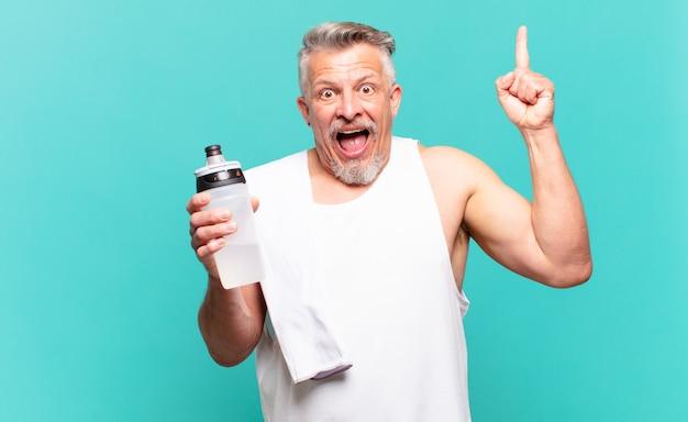 Starszy sportowiec czując się jak szczęśliwy i podekscytowany geniusz po zrealizowaniu pomysłu, radośnie podnosząc palec, eureka!