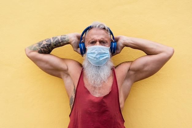 Starszy sportowiec mężczyzna w masce medycznej na twarz w celu zapobiegania koronawirusowi podczas słuchania muzyki z listy odtwarzania