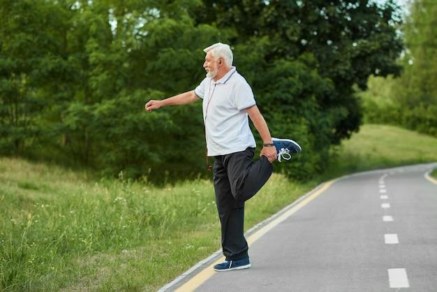 Starszy sportowiec robi ćwiczenia rozciągające na torze wyścigowym w mieście.