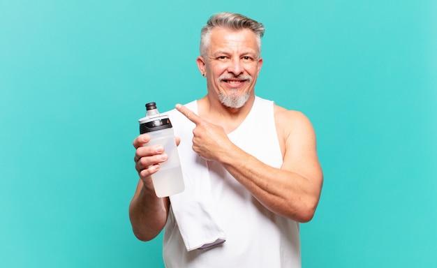 Starszy sportowiec uśmiechający się radośnie, czujący się szczęśliwy i wskazujący na bok i do góry, pokazujący obiekt w przestrzeni kopii
