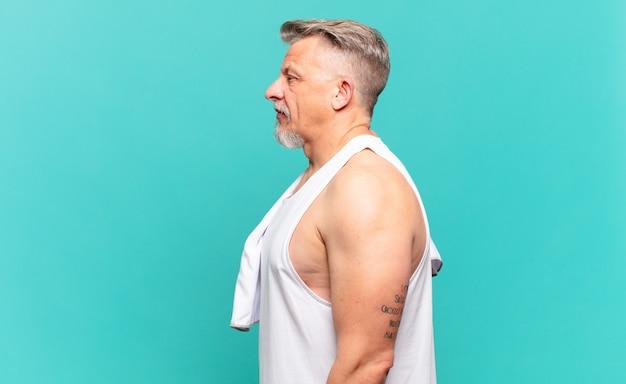 Starszy sportowiec w widoku profilu, który chce skopiować przestrzeń do przodu, myśląc, wyobrażając sobie lub marząc na jawie