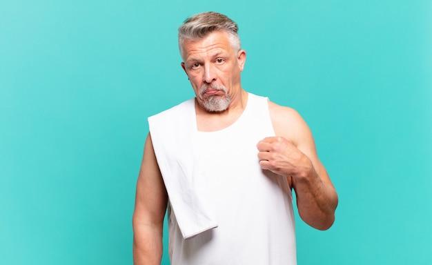 Starszy sportowiec wyglądający arogancko, odnoszący sukcesy, pozytywny i dumny, wskazujący na siebie