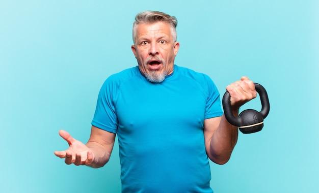 Starszy sportowiec z otwartymi ustami i zdumiony, zszokowany i zdumiony niewiarygodną niespodzianką