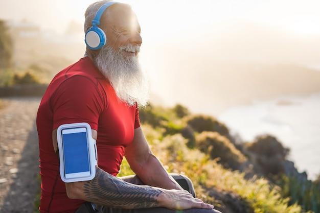 Starszy sprawny człowiek odkryty o zachodzie słońca po treningu