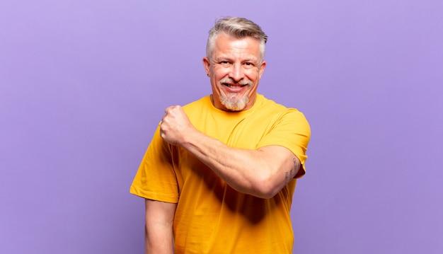 Starszy starszy mężczyzna czuje się szczęśliwy, pozytywnie nastawiony i odnosi sukcesy, jest zmotywowany, gdy staje przed wyzwaniem lub świętuje dobre wyniki