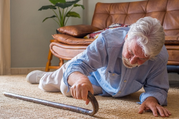 Starszy starszy mężczyzna leżący na podłodze po upadku z drewnianą laską obok kanapy na dywanie w salonie w domu. staruszek cierpiący z bólu i próbujący wstać po upadku w domu