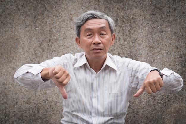 Starszy staruszek daje podwójne kciuki w dół gestowi