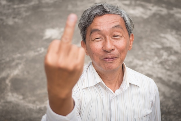 Starszy staruszek odwraca środkowy palec