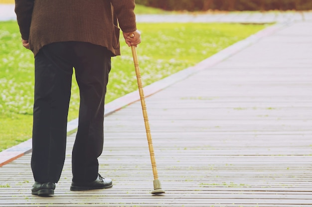 Starszy staruszek z laską stoją na chodniku chodnik przechodząc przez ulicę sam na poboczu drogi w parku publicznym