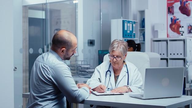 Starszy stary lekarz kobieta przepisuje nowe dawkowanie leków pacjentowi płci męskiej. opieka zdrowotna w nowoczesnym szpitalu lub przychodni prywatnej, profilaktyka chorób i konsultacje w gabinecie lekarskim leczenie diagnostyka leków