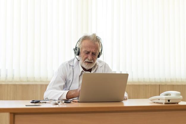Starszy stary lekarz nosi zestaw słuchawkowy. zdalne konsultacje medyczne online na czacie, usługi telemedyczne na odległość. koncepcja telezdrowia