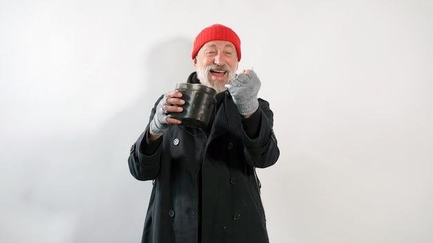 Starszy starzec, żebrak, bezdomny z siwą brodą uśmiecha się, trzymając w dłoni dolary na odosobnionej białej ścianie