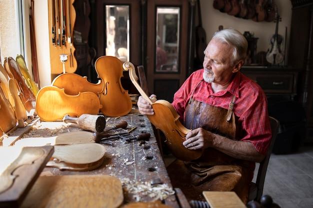 Starszy stolarz montujący elementy instrumentu skrzypcowego w swoim warsztacie stolarskim