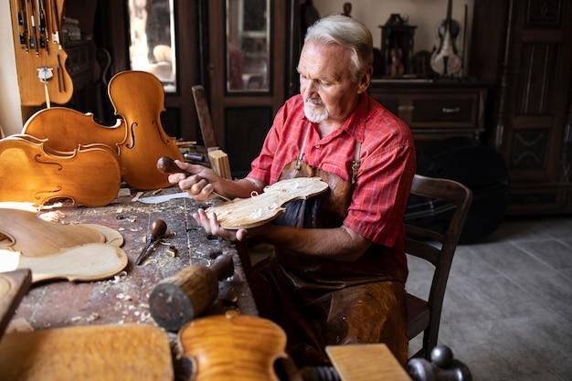 Starszy stolarz, rzemieślnik rzeźbiący w drewnie i robiąc instrument skrzypcowy