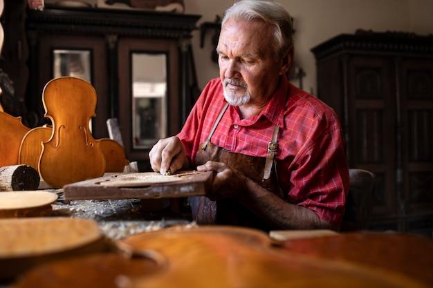 Starszy stolarz starannie rzeźbi i formuje drewno w swoim warsztacie stolarskim.